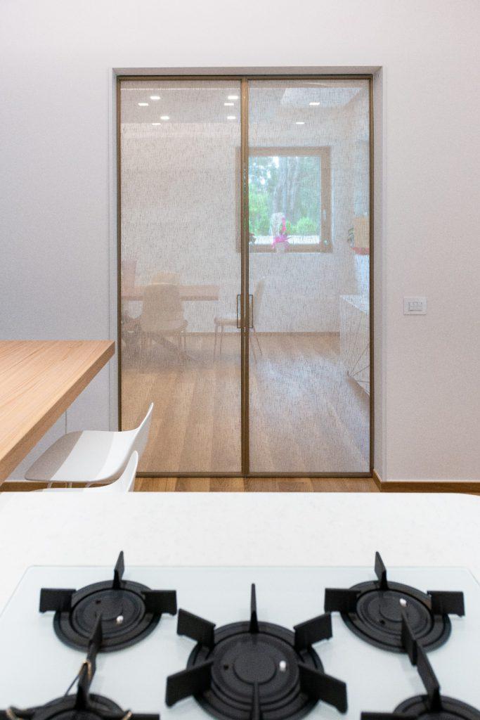 Porta scorrevole esterno muro doppia anta con vero tessuto di lino vista cucina